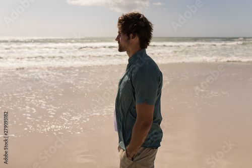 Young man with hand in pocket standing on beach