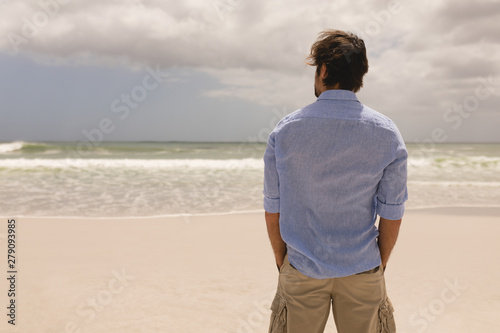Man standing with hands in pocket on the beach