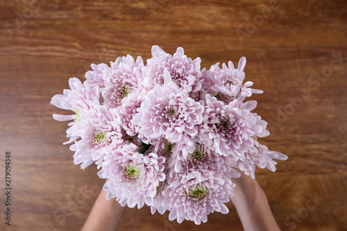 Hand of woman holding a bouquet of pink gerbera