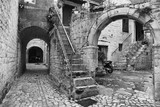 Fototapeta Uliczki - Black and white shot with high contrast of historic narrow street with tunnels and stairs made with stones, Croatia