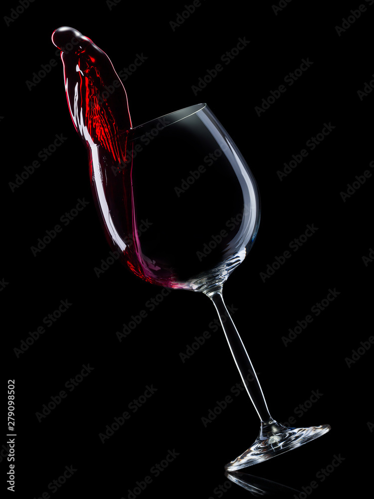 Fototapety, obrazy: Glass for red wine with splashes isolated on black background.