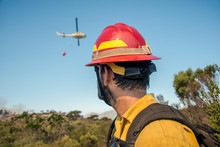 Wildland Firefighter Watching Turning Helicopter At Wildfire