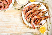 Grilled Big Tiger Shrimps Prawns On White Plate With Spices, Lemon, Fresh Herbs On White Wooden Background, Top View. Grilled Seafood. Barbecue Shrimps. Copy Space.