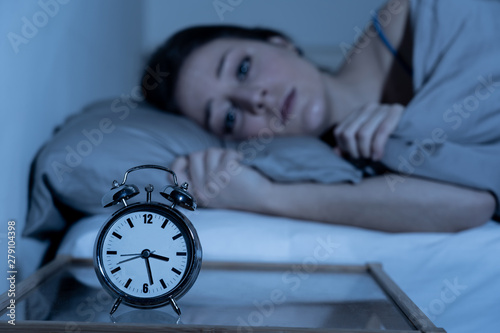 Canvas Print Attractive woman in bed staring at alarm clock trying to sleep feeling stressed