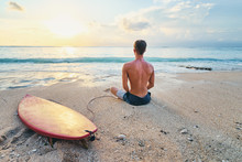 Surfing And Meditation. Enjoying Sunset.. Relaxed Young Man Siiting On Lotus Position With Surf Board On The Beach.