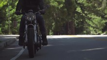 Slow Motion Of Motorcyclist With Leather Jacket Coming To A Stop On A Wooded Road