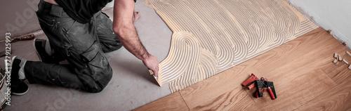 Fotografia Handwerker verlegt Parkettboden und streicht den Estrich mit Kleber ein und schl