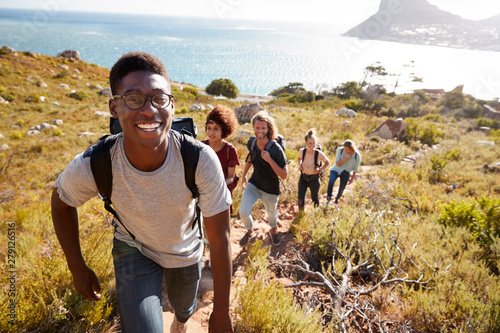 Fényképezés Millennial African American man leading friends hiking single file uphill on a p