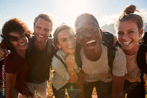 Fotografiet  Young adult friends on a hike celebrate reaching the summit, smiling to camera,