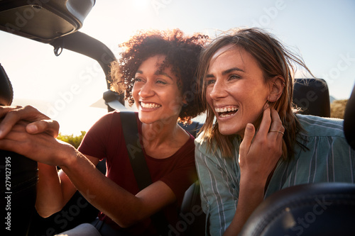 Two millennial female friends on a road trip smiling in the back of an open top car, close up - 279127395