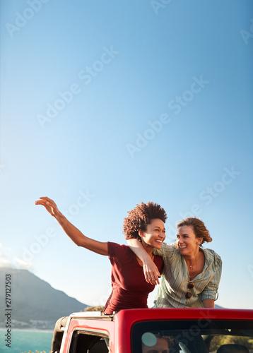 Fototapeta Two millennial female friends on a road trip standing in the back of an open top