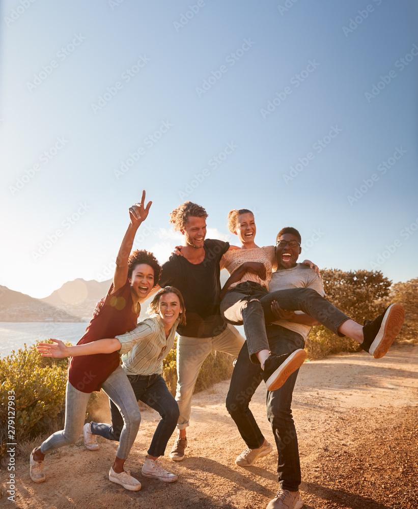 Fototapeta Five millennial friends on a road trip have fun posing for photos on a coastal path, full length