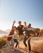 canvas print picture - Five millennial friends on a road trip have fun posing for photos on a coastal path, full length