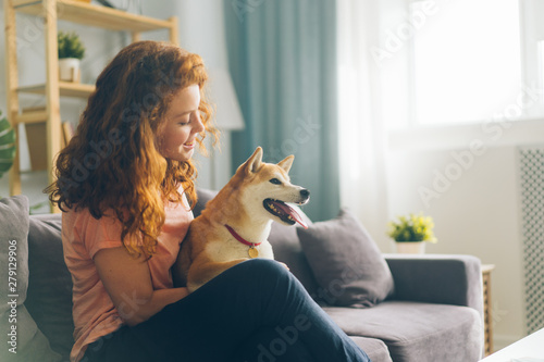 Photo Pretty redhead woman is hugging cute doggy sitting on couch in apartment smiling enjoying beautiful day with beloved animal