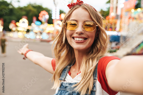 Poster Attraction parc Cheerful happy young blonde woman in amusement park take selfie by camera.
