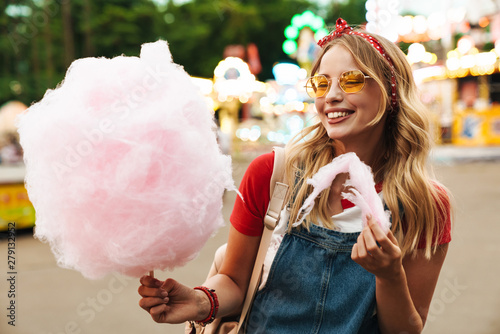 Wall Murals Amusement Park Image of happy blonde woman eating sweet cotton candy while walking in amusement park