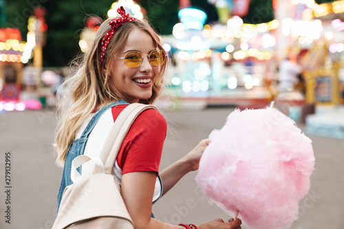 Image of smiling young woman eating sweet cotton candy while walking in amusemen Fototapeta