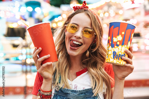 Photo Image of happy charming woman holding popcorn and soda paper cup while walking i