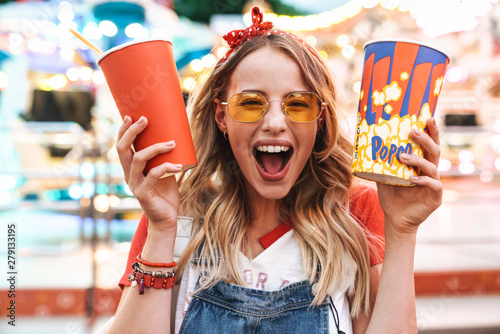 Obraz Image of joyful charming woman holding popcorn and soda paper cup while walking in amusement park - fototapety do salonu