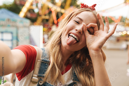 Fotografie, Obraz  Image of happy blonde woman showing ok sign and taking selfie photo at amusement