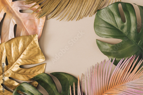 Fotografía  Creative layout made of colorful and golden tropical leaves and palms on beige background