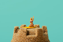 Miniature Woman On A Sandcastle
