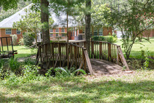 Large Lush Lot Backyard Of American House In The Suburbs With A Wooden Bridge Over A Small Creek