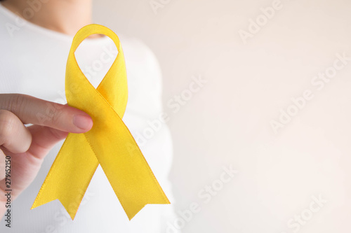 Stampa su Tela Young female holding yellow gold ribbon awareness symbol for endometriosis, suicide prevention, sarcoma bone cancer, bladder cancer, liver cancer and childhood cancer concept