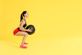 Fitness workout. Woman exercising squats with med ball at studio