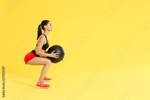 Fitness workout  Woman exercising squats with med ball at studio