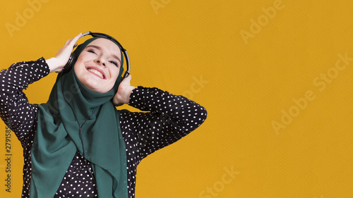 Happy muslim woman listening songs on headphone against yellow surface - 279158568