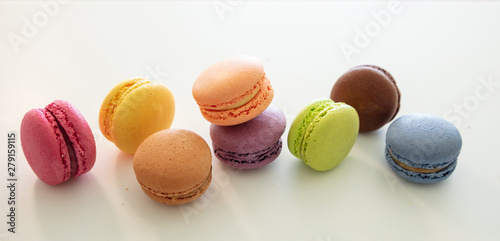 Colorful macarons on white background, close up view