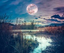 Landscape At Night Time In The Forest Lake With Fogy And Darkness Sky Super Moon In The Background.