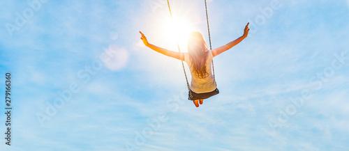 Fototapeta Frau auf einer Schaukel mit blauem Himmel im Gegenlicht obraz