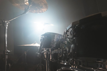 Close-up black drums A modern drum set prepared for playing in a dark rehearsal room on stage with a bright spotlight. The concept of percussion musical instruments