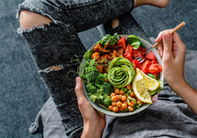 Woman In Jeans Holding Buddha Bowl With Salad, Baked Sweet Potatoes, Chickpeas, Broccoli, Greens, Avocado, Sprouts In Hands. Healthy Vegan Food, Clean Eating, Dieting, Top View