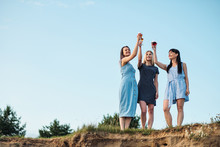 Three Young Attractive Women, In Blue Dresses Are Walking Along The Seashore. Girlfriends Communicate, Laugh And Drink Wine.