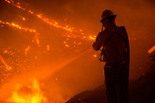 Silhouette Of Wildland Firefighter Battling Wildfire At Night