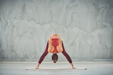 Fit Caucasian Brunette  In Sportswear Standing On The Exercise Mat In Studio And Doing Wide Legged Forward Bend Yoga Pose.