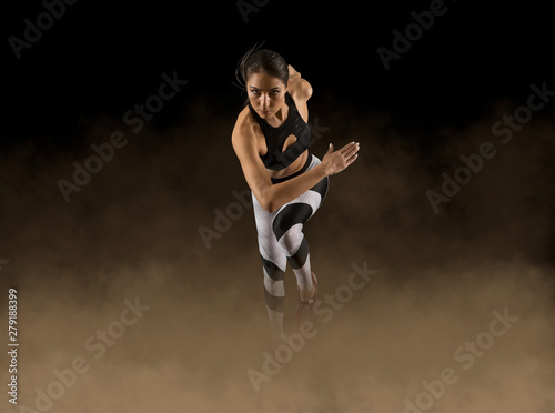 Cuadros en Lienzo Sporty woman running. Smoke background