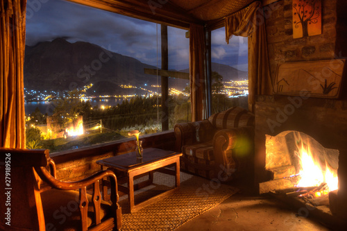 Foto Interior of a cozy cabin at night, with a lit fireplace and a beautiful view of the San Pablo lake and Imbabura volcano, Ecuador