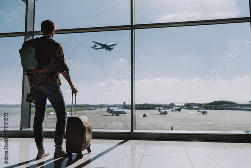 Photo Man is watching plane flying from airport