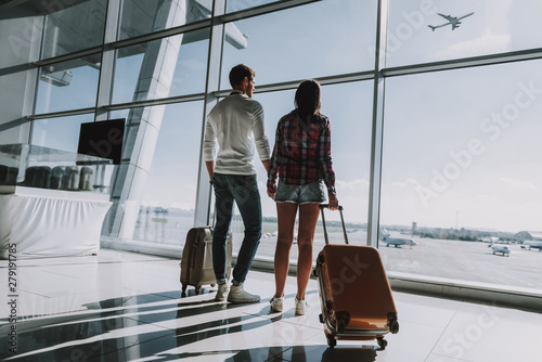 Loving couple is waiting for flight at airport Obraz na płótnie