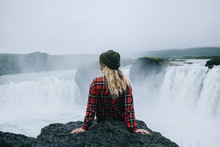 Beautiful Young Solo Female Adventurer Or Tourist Rests On Edge Of Cliff Or Mountain Overlooking Epic Waterfall. Concept Explore More, Scandinavian Tourism And Path Less Travelled