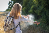 Woman tourist applying mosquito repellent on hand during hike in nature. Insect repellent. Skin protection against tick and other insect.