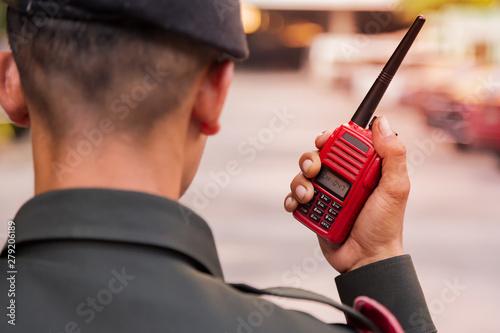 Security guard uses radio communication for facilitate traffic Tablou Canvas