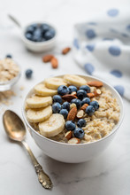 Oatmeal Porridge With Blueberries, Almonds And Banana On Marble Table