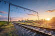 canvas print picture - Railway station and beautiful sky at sunset. Summer rural industrial landscape with railroad, blue sky with colorful clouds and sunlight, green grass. Railway platform. Transportation. Heavy industry