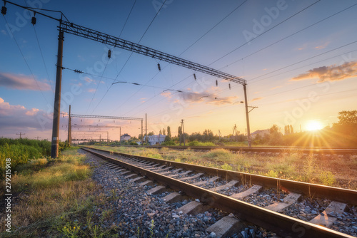 Montage in der Fensternische Eisenbahnschienen Railway station and beautiful sky at sunset. Summer rural industrial landscape with railroad, blue sky with colorful clouds and sunlight, green grass. Railway platform. Transportation. Heavy industry