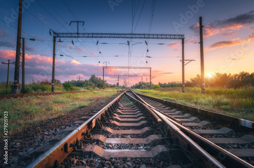 Foto auf Leinwand Blaue Nacht Railway station and beautiful sky at sunset. Summer rural industrial landscape with railroad, blue sky with colorful clouds and sunlight, green grass. Railway platform. Transportation. Heavy industry